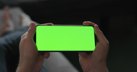 Slow motion man hold smartphone with green screen while lying on a couch