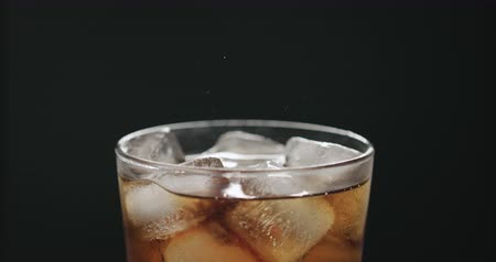 Slow motion cola in glass with ice cubes on black background closeup Wideo