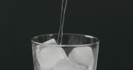 Slow motion pour soda in glass with ice cubes on black background closeup