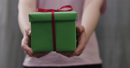 рекламный : Slow motion young woman stand and show green gift box with red ribbon bow