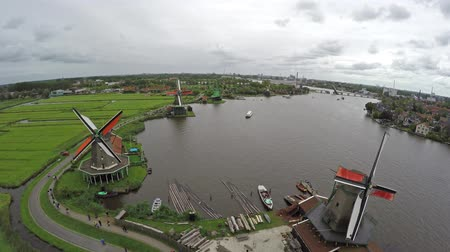 amsterodam : Zaandam Zaanse Schans aerial bird eye view helicopter flying away backwards showing windmills one of the most popular tourist attractions in the Netherlands Holland wooden barns mills houses museums Dostupné videozáznamy