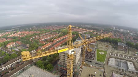 áruk : Aerial of yellow tower building crane fly around construction site building apartments real estate from a helicopter bird eye view houses, city and cloudy sky in background 4k Stock mozgókép