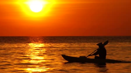 küçük sandal : Sunset sundown and a man canoe paddles his small boat across the sea lake showing a beautiful romantic style big golden sun and a quiet sea straight horizon and only showing silhouette of man rowing
