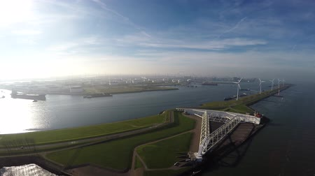 renovável : Aerial view of Rotterdam Harbor bird above Maeslantkering storm Barrier New Waterway waterway ook showing oil storage and wind turbines generating renewable energy piece of Delta Works Works 4k