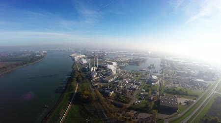 river ocean : Aerial view bird flying over dense industrial area industry showing the emissions coming from large buildings on the ground on the left a large canal for large oil tankers and container ships 4k Stock Footage