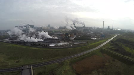район : Drone arriving at a industrial area showing some green grass but ook the heavy thick smoke and chimney exhaust pollution manufacturing steel mining dirty environment not clean pipes white smoke 4k