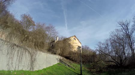 evacuated : Dolly shot of old abandoned house on a hill in creepy forest site showing a concrete wall and some trees of the forest of blue sky yellow building very stable smooth footage 4k quality high resolution Stock Footage