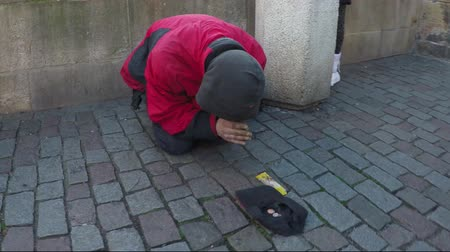 modlitba : Dolly Shot or beggar on streets praying for money and a passer by giving coins throwing them in hat laying on old street man kneeling forward does prayer When cash gets stabilized 4k high resolution