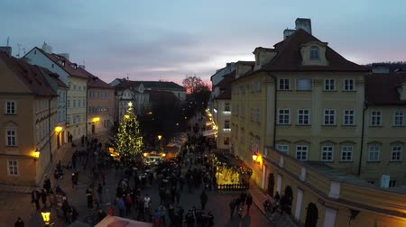 winter place : Prague Christmas market view from upstair from Charles Bridge early evening sun down and a lot of people visiting the small market ook showing the warm yellow light or lantarns and people browsing 4k