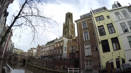 homeopático : Dom Tower and sound footage of typical dutch canal houses in Utrecht old city center showing the canal and the colorful homes ook showing the Dom Tower in background popular place for tourismt 4k