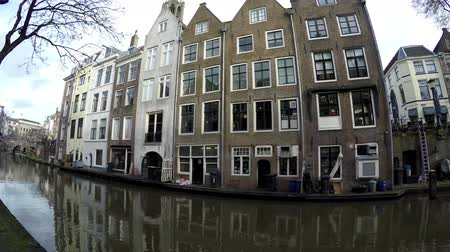 homeopático : Dolly Shot or typical dutchcanal houses in Utrecht old city center showing the canal and the colorful homes ook showing the Dom Tower in background very popular place for tourists to visit 4k Stock Footage