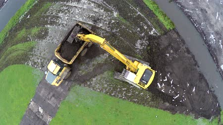 hernyó : Aerial top down view of a hydraulic excavator loading dump truck in mud sand excavating digging ground turning arm and loading the material into dump trucks yellow color machines at construction site 4k Stock mozgókép