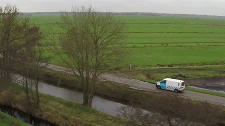 straight road : Aerial close up of white moving behind trees rural road driving delivery truck straight road Following drone same vehicle speed footage from leftvback side of moving car package delivery
