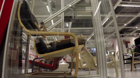 walmart : Modern testing equipment robot testing a chair behind glass showing the pushing robot arms imitate a human being sitting down and getting up quality control to Ensure the build of the furniture 4k