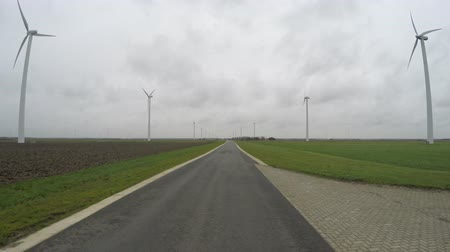 Флеволанд : Wind turbines on right and left side of road driving over it in first person view polderlandscape flatland and in background several at more aerofoil wind-powered generator creating renewable energy 4k Стоковые видеозаписи