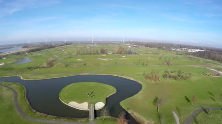 clubhouse : Aerial drone flying over golf course fairway green grass and lake with small round island with golf players walking on it usefull showing bunkers and Further overview of golf field beautiful birdview 4k