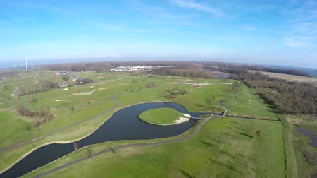 clubhouse : Aerial view of golf course and lake island beautiful green grass fairways and surrounding landscape swamp and forest nice day blue sky and bright contrasting colors springtime bird-eye view birdview 4k