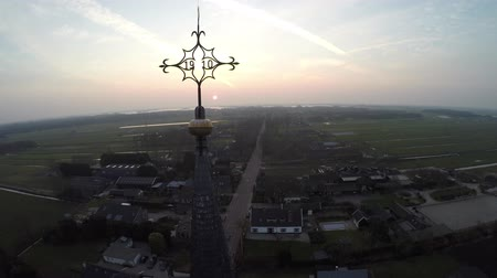equinox : Aerial flight dusktime moving near top of church tower beautfiul sky with vapor trails contrails condensation trails in background Church is located in the small village usefull some moving cars below 4k Stock Footage