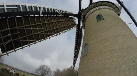 famous pace : Footage of a typical dutch windmill sails moving by wind at a steady pace recorded video standing nearby the large building at first floor bookable to get close to the blades of the mill tourist visit 4k Stock Footage
