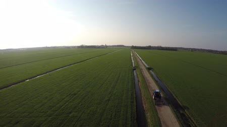 stimulating : Aerial moving fast and low over tractor heading home on gravel road landscape and blue sky background fresh green grass field footage steady blue tractor agricultural machinery heading for farm 4k