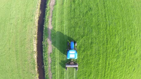 stimulating : Aerial above top down view Tractor farmer flattening land using roller agricultural tool used for flattening land or breaking up large clumps of soil blue sky background beautiful rural landscape 4k