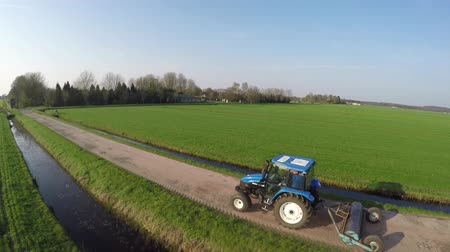 stimulating : Aerial leftback Tractor farmer heading home gravelroad beautiful landscape scenery blue sky background fresh green grass field footage steady blue tractor agricultural machinery heading for farm 4k Stock Footage