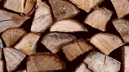 timberland : Footage of large pile of chopped wood pieces piled neatly onto one eachother warm typical dark brown wood color stacked wood is dried and ready for use in the fireplace at colder winter months 4k quality Stock Footage