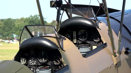 wwi : Zoom out footage of an old world war one airplane biplane fixed-wing aircraft with two main wings stacked one above the other place for two people to pilot plane very good condition grass airfield 4k