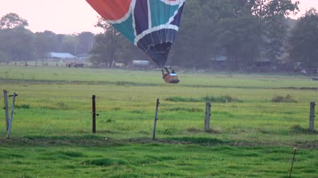 equinox : Hot air balloon landing on grassland moving low then touching down on land showing the burner flame heating the baloon and the pilot in basketball pointing out a place to land moving steady and low 4k Stock Footage