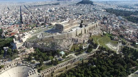 dionysus : Aerial drone bird-eye view moving around back of the Acropolis of Athens ancient citadel located on rocky outcrop showing Parthenon very famous tourist attraction in Europe Greece European visit 4k