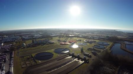 kanalizacja : Aerial flying towards sun on wastewater treatment plant also known as sewage treatment plant or sewage treatment plant works for sewage treatment process of removing contaminants from wastewater 4k