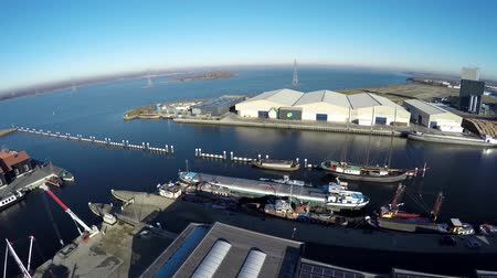 dry zone : Aerial drone flying over industrial area on first shipyard dry dock for recreational boats then on several at ships docked towards lumber mill and white warehouses great beautiful weather blue sky 4k Stock Footage