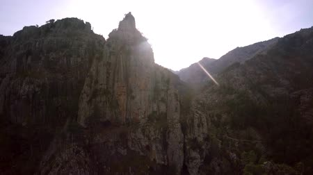equinox : Aerial of mountain peak with sun shining bright behind it rocky environment showing color gray rock and some vegetation in between beautiful day bright sun and clear sky behind Mount formation 4k Stock Footage