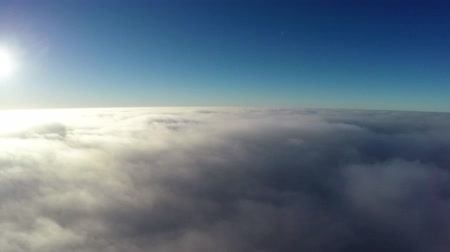 uçan : Aerial bird-eye view flying steady altitude above thick clouds towards bright sun beautiful contrast showing crisp blue sky above the darker atmosphere bright sunshine and slowly moving clouds below