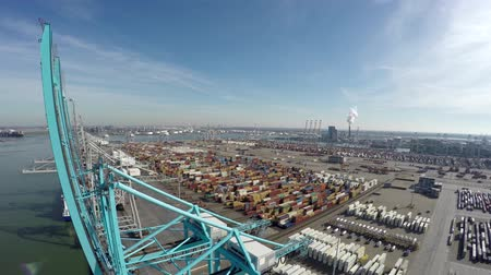 mezinárodní : Aerial view bird flying over harborareaparanormal fits blue harbor cranes for loading or unloading intermodal containers in background a container terminal with containers ready for transport blue sky 4k