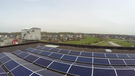 Флеволанд : Aerial flight low altitude and backwards birdview on sustainable roof of modern building with solar panels designed to absorb suns rays as source of energy for generating electricity or heating 4k