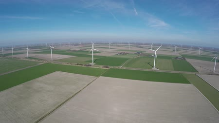 еще : Aerial over polderlandscape below empty fields with no vegetation on it yet usefull showing wind turbines producing renewable energy windmills producing electricity and in agricultural land aera 4k Стоковые видеозаписи
