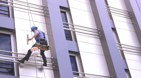 risco : modern office building Workers washing the windows facade - Industrial alpinist climbers  Vídeos