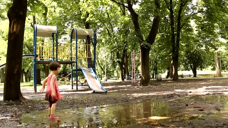 bahno : cute little girl playing in the puddle of mud on the playground in the park Dostupné videozáznamy