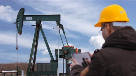 crude : Pump oil jack with worker and clouds Stock Footage