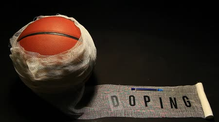 dose : basketball with bandage, syringe and doping text on dark background