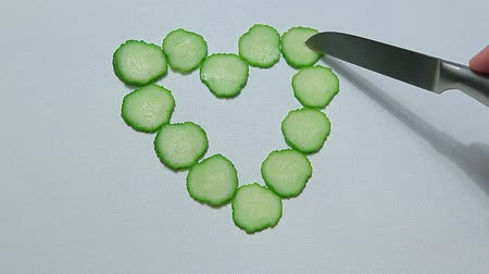 pepino : cucumber heart symbol knife white background hd footage