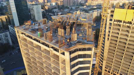 строительные леса : Top of high tower building with workers on construction site. Big city development. Metropolis. Aerial view Стоковые видеозаписи