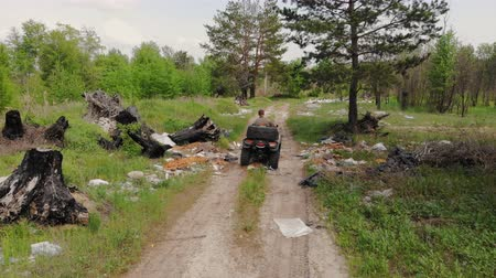 quadbike : Following back view of environmental inspector or forester riding atv quadbike through forest polluted with plastic and other different garbage. Illegal waste landfill. Global earth pollution problem