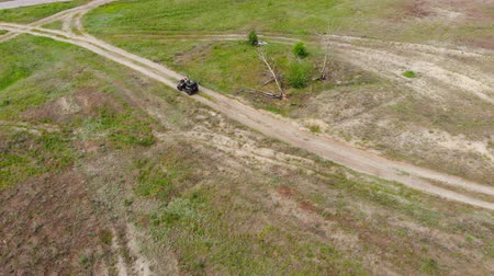 atv : Top-down aerial view of young adult man riding an ATV quad bike over country rough terrain road with meadows of dry autumn grass and green coniferous tree forest. Adventure sport activity concept