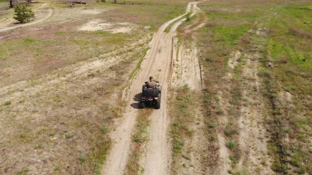 quad bike : Top-down aerial view of young adult man riding an ATV quad bike over country rough terrain road with meadows of dry autumn grass and green coniferous tree forest. Adventure sport activity concept