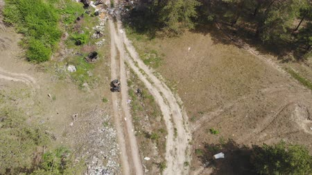 quadbike : Top-down view of environmental inspector or forester riding atv quadbike through forest polluted with plastic and other different garbage. Illegal waste landfill. Global earth pollution problem