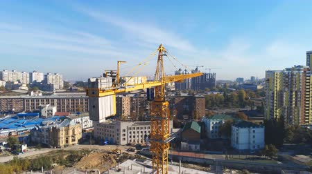 High building construction site. Big industrial tower crane with blue sky amd cityscape on background. Concrete plates weight balance. Counterweight. Aerial drone view. Metropolis city development Vídeos