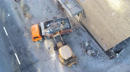 Bulldozer loader uploading waste and debris into dump truck at construction site near road. building dismantling and construction waste disposal service. Aerial drone industrial background