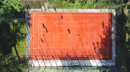 Aerial top-down view friends playing basketball at outdoor open court in city park. Drone overhead footage